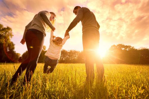 parents swinging a child in an open field at sunset