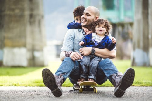 A Hispanic man with his two young sons riding on a skateboard.