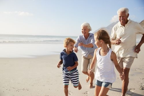 Grandparents Running Along Beach With Grandchildren